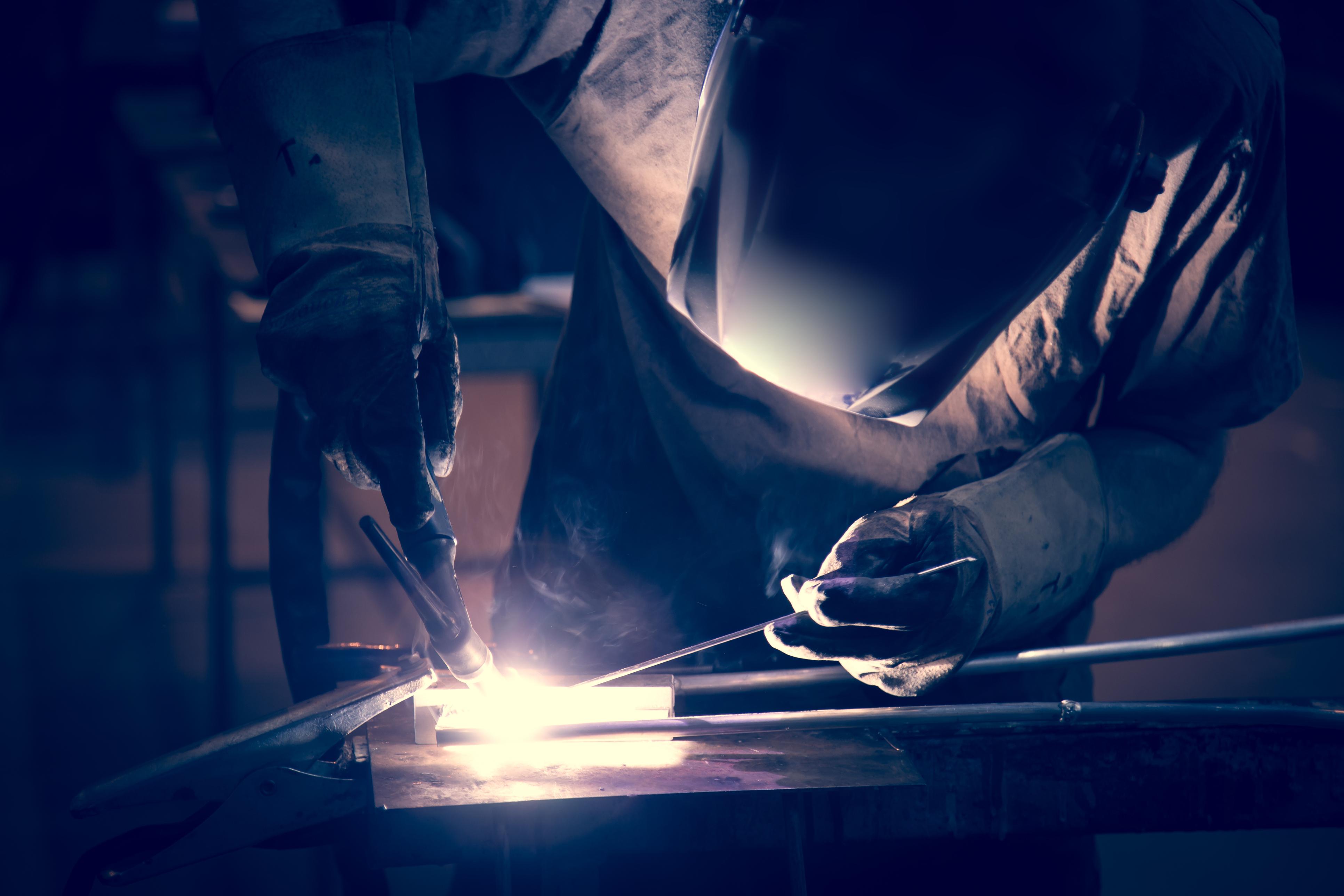 Employee welding aluminum using TIG welder in workshop.